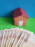 European banknotes, figure of a house on green surface and blue background. Backdrop for mortgage and housing value ads, loan for home construction and stock image