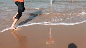 European bearded man running on sea beach. Freedom concept. Male tourist runs barefoot on amazing summer seashore. 4K. stock video footage