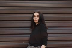 European beautiful young brunette woman in stylish black sweater in trousers posing standing near a brown metal vintage building. On a spring day. Modern stock photo