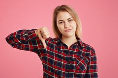 European beautiful young woman dissatisfied with something, disapproves somebody`s work, keeps thumb down, shows dislike sign, iso royalty free stock images
