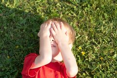 European blond boy closed his eyes with his hands lying on the grass royalty free stock photography