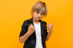 European Blond Boy In A Black Leather Jacket And A White T-shirt With A Bandana Holds His Fists On A Orange Background Royalty Free Stock Image