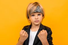 European Blond Boy In A Black Leather Jacket And A White T-shirt With A Bandana Holds His Fists On A Yellow Background Stock Photos