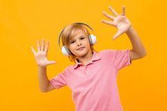 Free European Blond Boy In A Pink T-shirt Comes Off To Music In White Headphones On An Orange Background Royalty Free Stock Images - 166172209