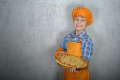European boy dressed as a cook holding a freshly prepared pizza against a gray wall stock photography