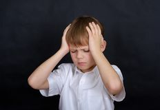 European boy holding his head. headache. Boy European appearance holding his head in pain. headache concept. isolate on a black background royalty free stock photos