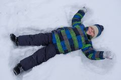 Boy lying in the snow and waving arms and legs stock photos