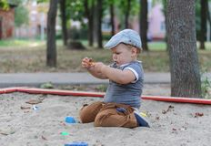 European boy playing in sandbox stock photo