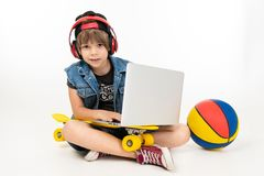 European Boy Sitting On The Floor With Laptop, Skateboard And Basketball On A White Background. Royalty Free Stock Images