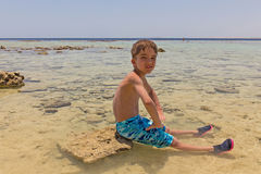European boy sitting in the shallow waters Royalty Free Stock Images