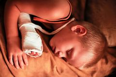 The European boy is sleeping after medical procedures. His arm is bandaged and plaster cast on he. R Royalty Free Stock Image