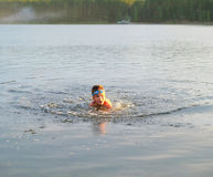 European boy swims in the evening lake Stock Photo