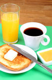 European breakfast: cup of coffee, toasts, jam, butter and orange juice Stock Images