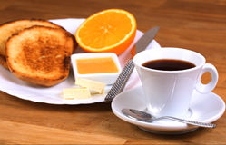 European breakfast: cup of coffee, toasts, jam, butter and orange Royalty Free Stock Photos