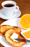 European breakfast: cup of coffee, toasts, jam, butter and orange Royalty Free Stock Image