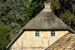 European building styles, timber framed. European building styles. detail of yellow timber framed house with white small windows and thatched roof royalty free stock photo