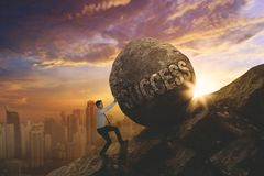 European businessman pushing success word. European businessman climbing on the cliff while pushing a stone with success word. Shot at sunrise time Stock Photo