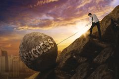 European businessman dragging success word. Picture of European businessman struggling to drag a stone with success word while climbing on the cliff Stock Photo