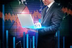 Technology and economy concept. European businessman with laptop on business chart background. Technology and economy concept stock photos