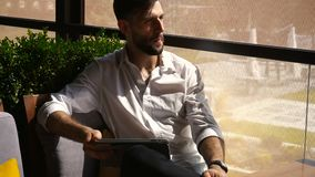 European businessman using tablet at cafe table. European businessman browsing  with tablet at cafe table. Young handsome man working in classic style white stock video