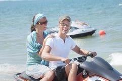 European Caucasian couple smiling on racing PWC at tourist hot spot beach of Terengganu. Stock Images