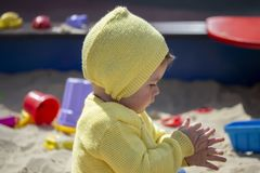 European child girl boy shakes his hands from the sand in the sandbox. Child baby one year old playing on the playground in the. Sandbox. Toddler in a yellow royalty free stock images
