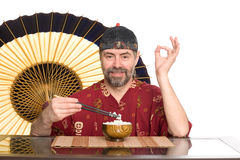 European in chinese attire eating rice Royalty Free Stock Photography