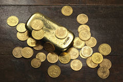 European circulation gold coins. Various European circulation gold coins from the 19th/20th century around a gold bar on rustic wooden background Royalty Free Stock Photography