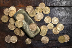 European circulation gold coins. Various European circulation gold coins from the 19th/20th century around a gold bar on rustic wooden background Stock Image