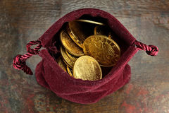 European circulation gold coins. Various European circulation gold coins from the 19th/20th century in a velvet purse on rustic wooden background Stock Images
