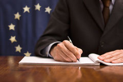 European Community. A man who signs up a document about the european community Stock Photography