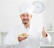European cook in cap offering oat porridge for breakfast Royalty Free Stock Photography