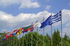 European countries flags waving. Across summer sky in green trees setting stock photography