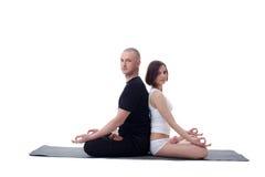 European couple doing yoga in studio Stock Photo