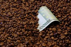 100 Euro banknote in the roasted coffee beans. European currency, 100 Euro banknote, laying in the roasted coffee beans royalty free stock photos