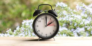 European daylight saving time. Alarm clock on wooden desk, blur spring nature background. 3d illustration. European daylight saving time end. Alarm clock on stock photo