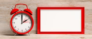 European daylight saving time. Red alarm clock and blank frame isolated on wooden background, banner. 3d illustration stock images