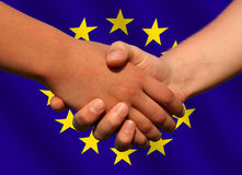 European deal. A handshake in front of a waving European Union flag Stock Photography