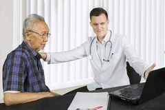 European doctor with medical report and patient royalty free stock images