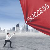 European employee struggling to pull success word. Picture of European male employee struggling to pull a banner with success word while standing at outdoor Stock Photos