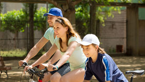 European family riding bicycles in park. And smiling Stock Photography