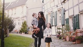 European family walk together. Mother and two kids. Slow motion. Woman, boy and girl hold hands smiling. Love and care. European family walk together. Mother stock video footage