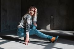 European fashionable young woman model in stylish jeans in green fashionable cowboy boots in a trendy shirt poses sitting. In a room with sunlight. Beautiful stock photography