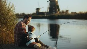 European father and son sit together on lake pier. Boy holds a hand made fishing tackle. Happy family relationships. 4K.