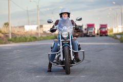 European female motorcyclist sitting on classic chopper on an asphalt road, front view Royalty Free Stock Image
