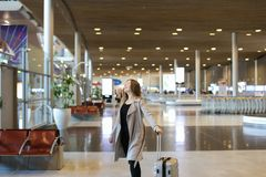 European female person wearing grey coat walking in airport hall. European female person wearing grey coat walking in airport hall with valise. Concept of Royalty Free Stock Image