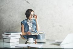 European female secretary at office desk. Portrait of european business woman or female secretary reading book or doing paperwork at desk with tools and items Stock Images