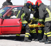 European firefighters in action and pull the injured from the ca Royalty Free Stock Photos