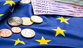 European flag and euro money. Coins and banknotes European currency freely laid on the Eur. Euro coins. Euro currency. Euro money. European flag and euro money stock image