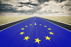 European flag, road perspective, dark clouds Royalty Free Stock Photo